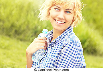 Happy woman with water over grass