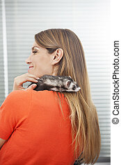 Happy Woman With Weasel On Shoulder - Rear view of happy mid...