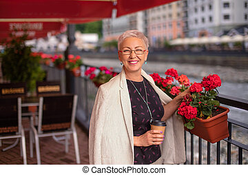 happy woman with wonderful flowers on the pot is posing to the camera