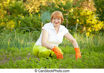 Happy  woman working in  vegetable garden