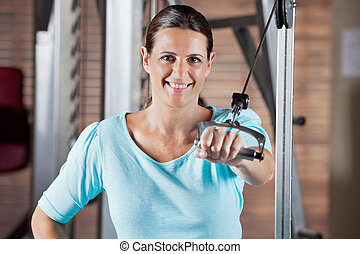Happy Woman Working Out In Health Club