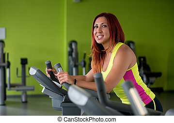 Happy woman working out on a gym cycle
