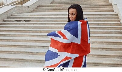 Happy woman wrapped in union jack flag in front of stairs...