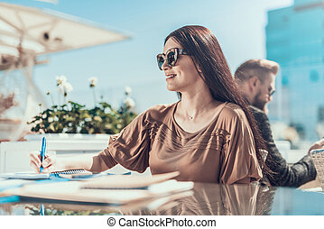 Happy woman writing in copybook during job