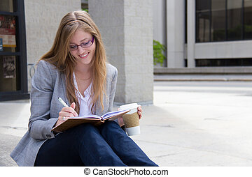 Happy woman writing in her notebook