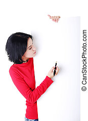 Happy woman writing with a pen on blank board