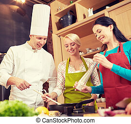 happy women and chef cook cooking in kitchen - cooking...