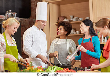 happy women and chef cook cooking in kitchen