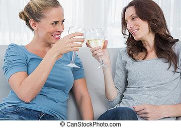 Happy women clinking their wine gla - Happy women looking at...