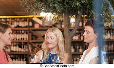 happy women drinking red wine at bar or restaurant - people,...