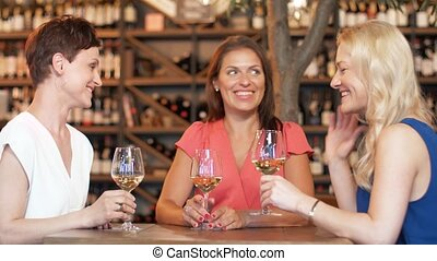 happy women drinking wine at bar or restaurant - people,...