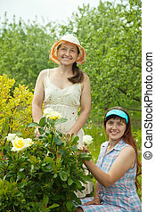 Happy women gardening with roses