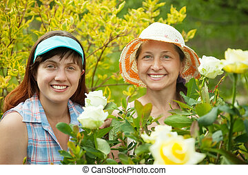 Happy women gardening with roses plant