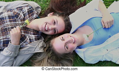 Happy women holding flowers while lying