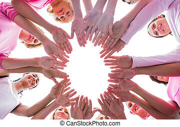Happy women in circle wearing pink for breast cancer on...