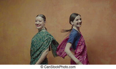 Happy women in indian sari whirling in dance - Cheerful...