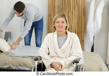 happy women in wheelchair with male assistant at home