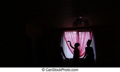 Happy women joyfully dance in hall in darkness. Casement is...