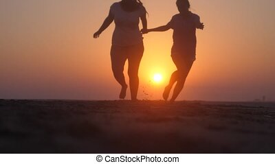 Happy women running at the beach on sunset in slow motion. Beauty and joyful teenager friends having fun.