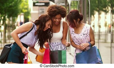 happy women showing shopping bags in city - sale,...