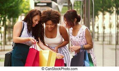 happy women showing shopping bags in city - sale,...