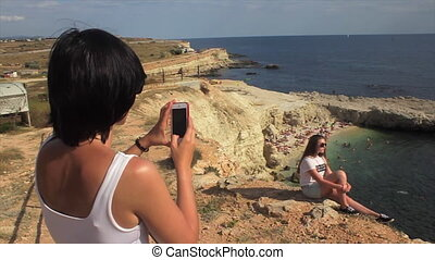 Happy women taking photo friend with smartphone on the background sea lighthouse