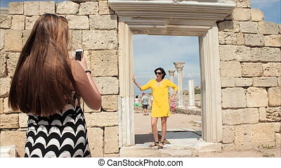 Happy women taking photo girl friend with smartphone on the ruins of the ancient city background