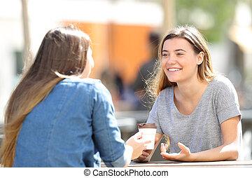 Happy women talking sitting in a park