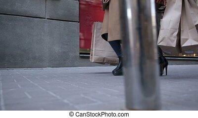 Happy women walking city street with shopping bags - Closeup...