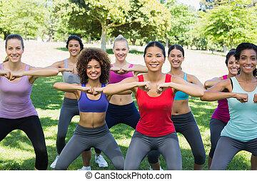 Happy women warming up in park