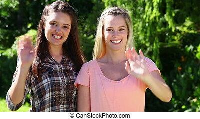 Happy women waving their hands
