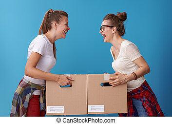 happy women with cardboard boxes looking at each other on blue