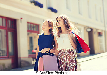 happy women with shopping bags walking in city - sale,...