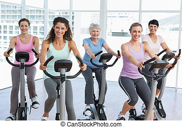 Happy women working out at spinning class - Group of happy...