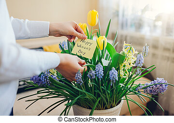 Happy Womens Day, 8 March gift. Woman found greeting card with blooming spring yellow blue flowers at home
