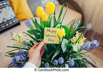 Happy Womens Day, 8 March gift. Woman holds greeting card with blooming spring yellow blue flowers at home
