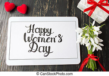 Happy womens day calligraphy note on a tablet