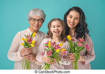 Happy women's day! Child daughter is congratulating mom and grandma giving them yellow flowers tulips. Granny, mum and girl smiling and hugging on light blue background. Family holiday and togetherness.