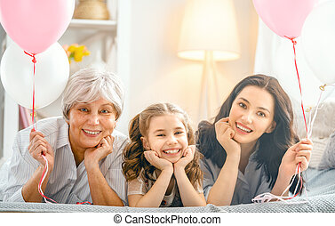 Happy women's day! Child, mom and granny with air balloons. ...