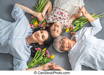Happy women's day! Child, mom and granny with flowers tulips...