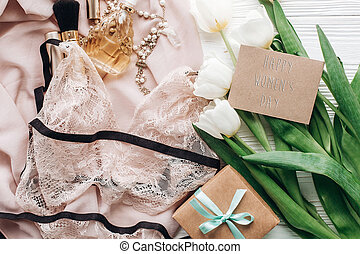 happy womens day text sign on woman lace lingerie jewelry and perfume present on soft fabric and tulips with empty greeting card on white rustic background. flat lay