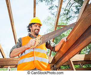 Happy Worker Cutting Wood With Handsaw At Site