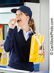 Happy Worker Eating Popcorn At Cinema Concession Stand