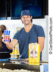 Happy Worker Holding Drink At Cinema Concession Stand
