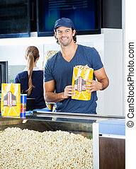 Happy Worker Holding Popcorn Paperbag At Concession Stand