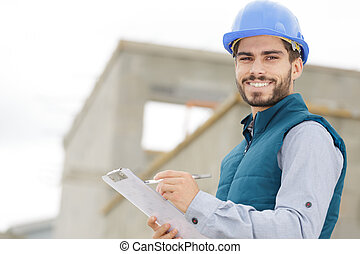 happy worker in a hard hat looking at camera