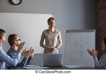 Happy workers applauding thanking businesswoman for presentation