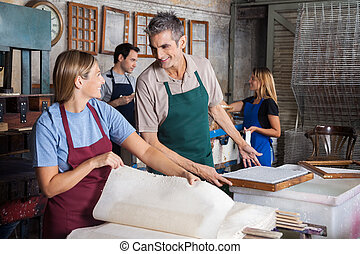 Happy male and female workers making papers while looking at each other in factory