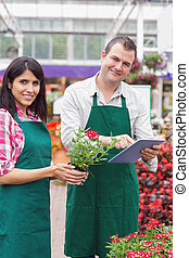 Happy workers with tablet pc in garden center - Happy...