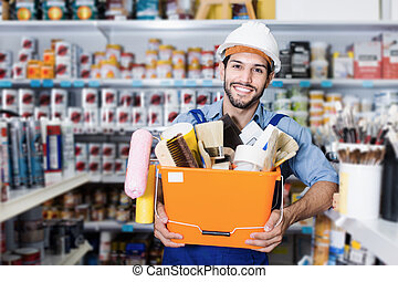 Happy workman with tools in paint store